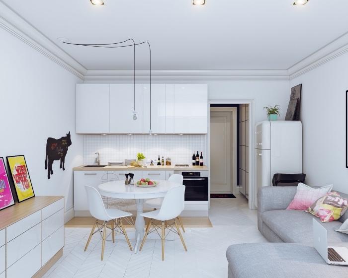 comment aménager un petit appartement, idée cuisine ouverte sur le salon, façade cuisine blanche, coin repas en table et chaises blanches, canapé d angle gris d angle, parquet blanchi, deco affiches vintage