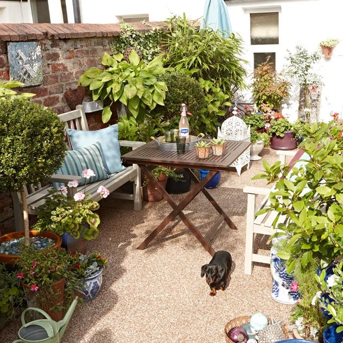 amenagement petit jardin, aptio salon de jardin, banc blancs et table en bois pliante, coussin décoratifs bleus, plusieurs fleurs et arbustes plantés dans des pots de fleurs