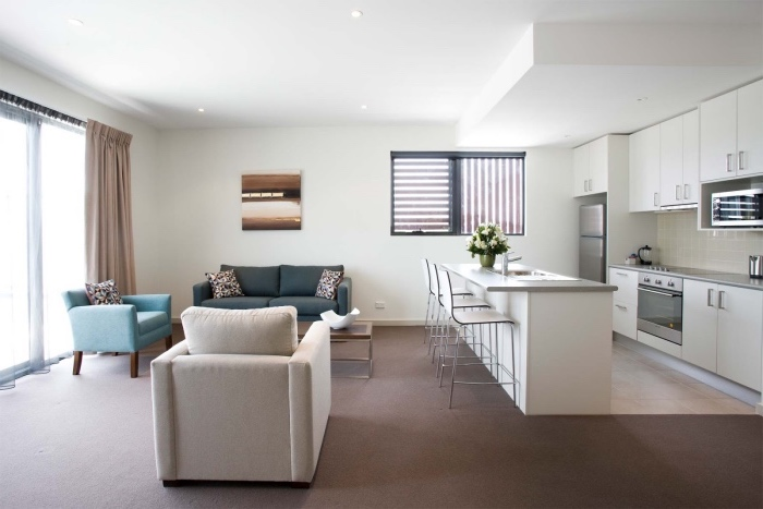 aménager une petite cuisine blanche ouverte sur un salon avec canapé gris, fauteuil bleu et fauteuil blanc cassé, tapis marron, separation cuisine salon ilot central