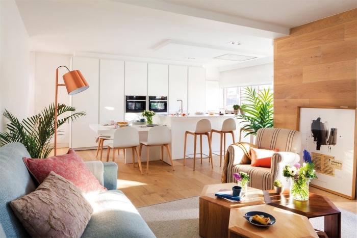 cuisine ouverte sur salon, façade cuisine blanche avec ilot central blanc, table salle à manger blanche et chaises blanches, parquet clair, salon canapé gris, coussins colorés, table basse en bois design