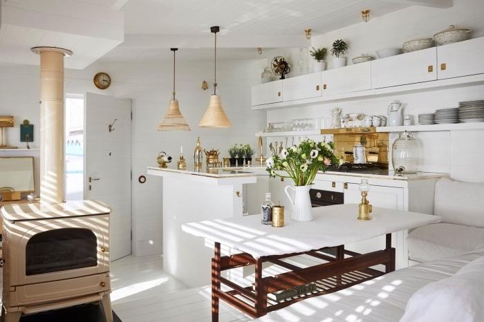 amenager petite cuisine style campagne chic avec facade blanche et ilot blanc, table en bois avec plateau blanc et canapé d angle adjacent, cheminée vintage, deco florale