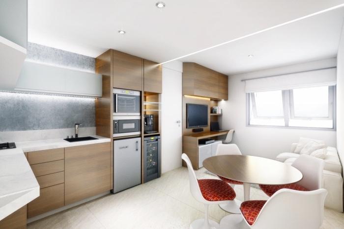 modele de cuisine americaine ouverte, facade en bois clair et électroménagers en inox, revêtement sol blanc, table en bois et chaises blanches, coin salon avec canapé blanc, meuble télé en bois