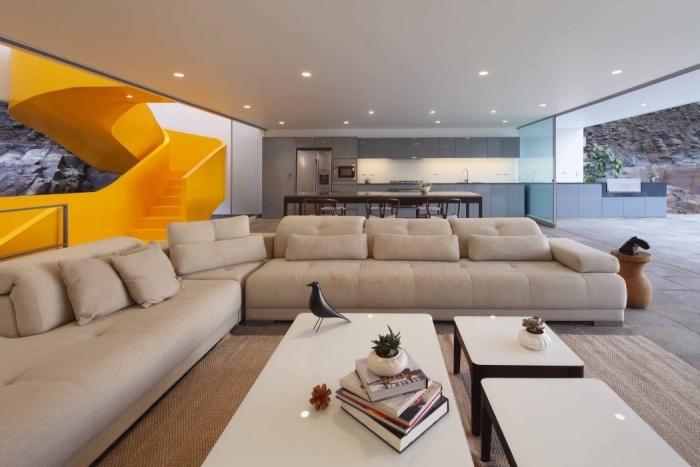 idée cuisine ouverte sur le salon, façade cuisine grise, table et chaises en bois, revêtement sol en dalles de béton, canapé gris clair, tables basses blanches, escalier tournant jaune design