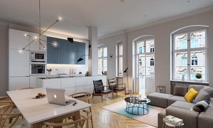 amenagement petite cuisine ouverte sur un salon, façade blanche avec des placards gris, salon avec canapé gris et tabale basse noire, coin repas table en bois massif et chaises bois