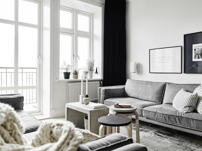intérieur scandinave, cadres photo en noir, canapé en tissu gris, plaid beige en crochet, murs peints en blanc