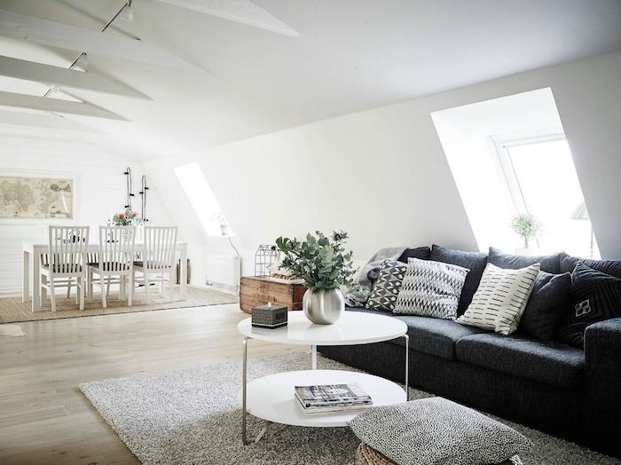 meuble scandinave, aménagement sous pente, armoire en bois, tapis moelleux gris, canapé noir, plantes vertes