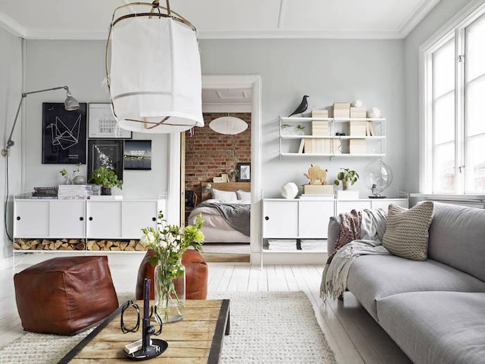 mobilier scandinave, parquet en bois peint en blanc, étagère murale blanche, canapé en tissu gris, pouf en cuir marron