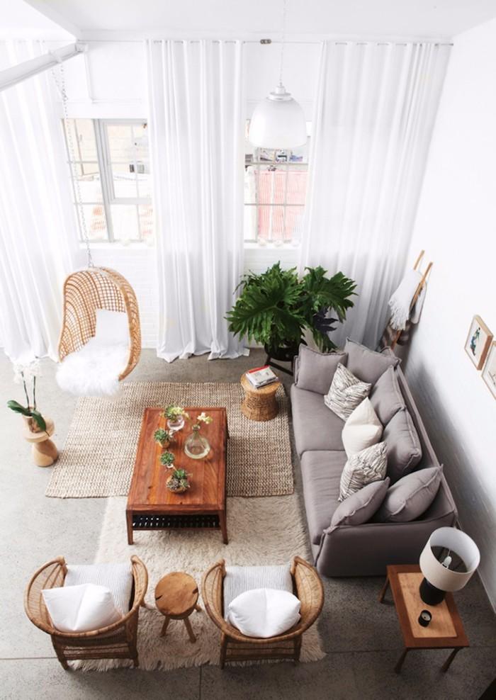 meuble scandinave, chaise suspendue en fibres végétales, canapé gris, plantes vertes, rideaux longs en blanc