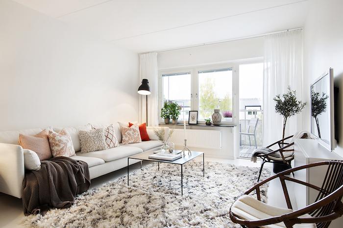 deco scandinave, chaise ronde, canapé blanc en cuir, tapis blanc et marron, rideaux longs, lampe sur pied noire