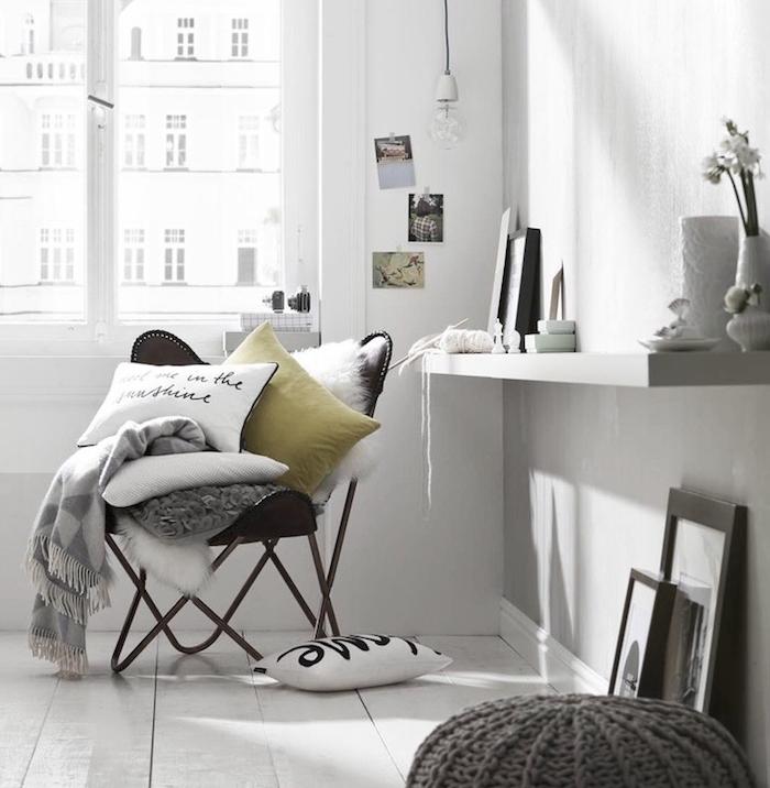 deco esprit scandinave, pouf en crochet gris, cadres photo noirs, murs blancs, chaise papillon noire avec coussins