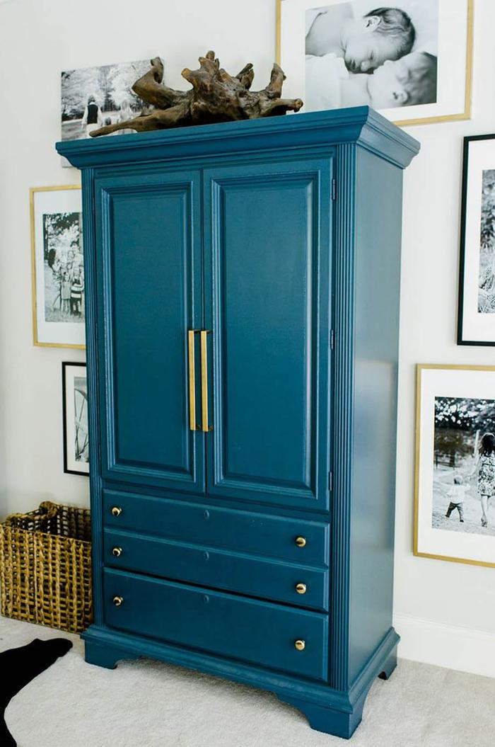 une jolie armoire peint bleu paon foncé mise en valeur par une galerie photos en noir et blanc