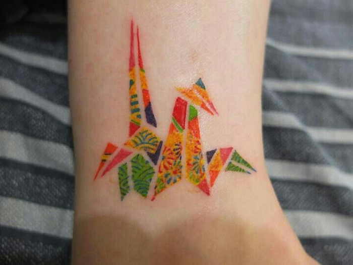 un discret tatouage minimaliste à motif grue colorée très réaliste