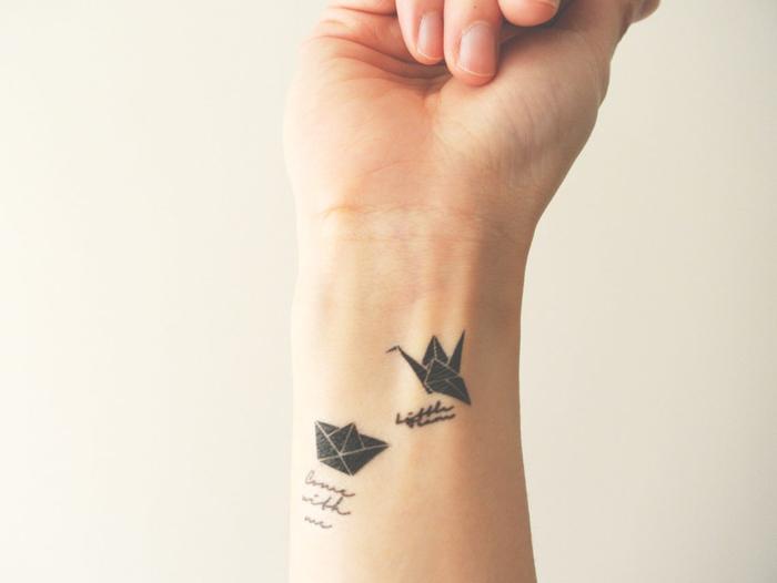 joli tatouage minimaliste au poignet composé d'une petite grue origami et d'un bateau en papier reliés à des mots calligraphiés