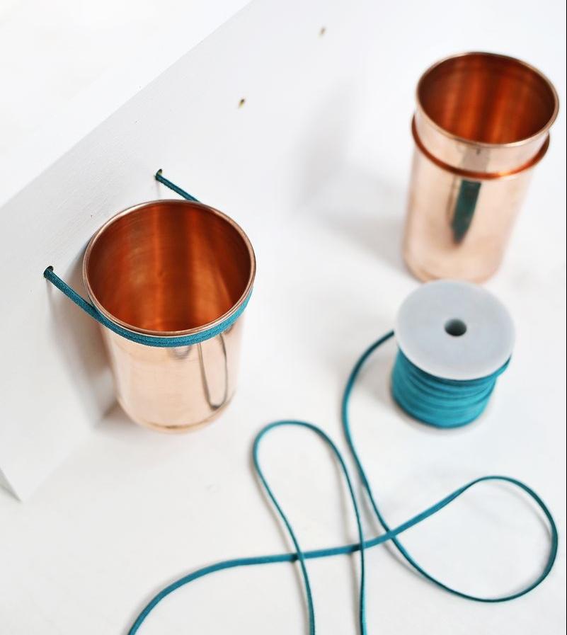 idée comment fabriquer un rangement maquillage mural, pots en cuivre fixés à une planche en bois avec un cordon en cuir, astuce rangement