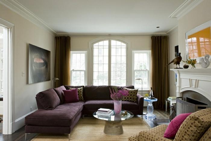 aubergine couleur, sofa d'angle pourpre, deux tables rondes de salon, cheminée décorative, tableau abstrait