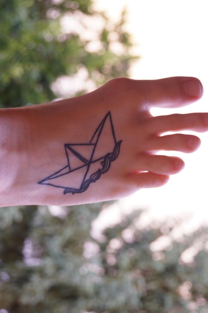 tatouage géométrique représentant un bateau en papier flottant sur les vagues