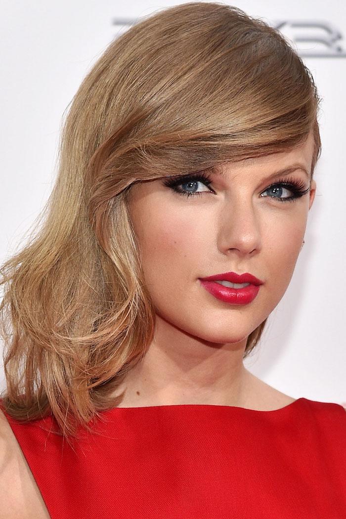 couleur de cheveux tendance, coiffure célébrité, Taylor Swift, cheveux mi longs avec frange de côté, rouge à lèvre et robe rouge