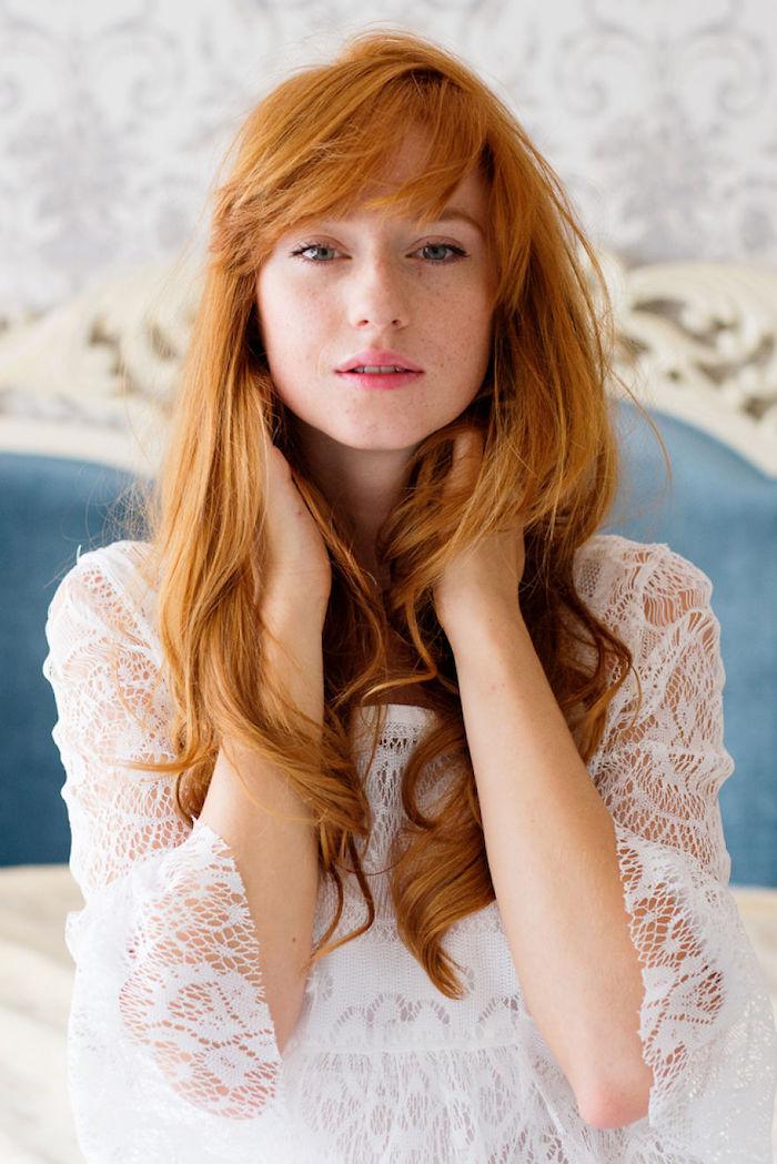 couleur rousse, tête de lit en blanc et bleu, femme aux cheveux longs et bouclés, maquillage naturel avec lèvres rose