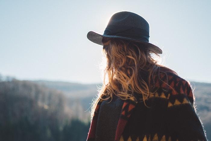 meche blonde, accessoire pour femme chapeau noir, coupe de cheveux longs en bronde, poncho noir à motifs triangulaires