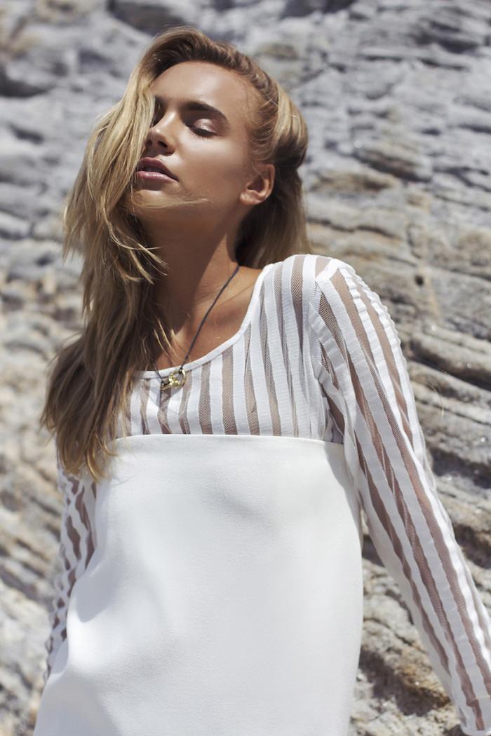 blond cendré, femme au bord de la mer au maquillage naturel, chemise blanche avec manches en lignes transparentes