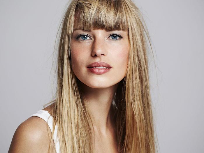 cheveux blond foncé, visage avec tâches de rousseur, coiffure cheveux lisses avec frange, yeux bleu et eye-liner noir