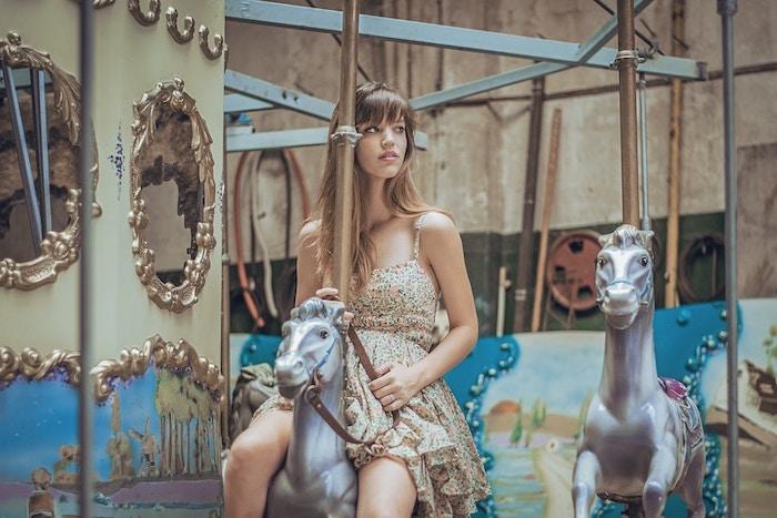 blond cendré, fille sur manège cheval, robe longueur genoux en beige avec petites fleurs en rose pastel