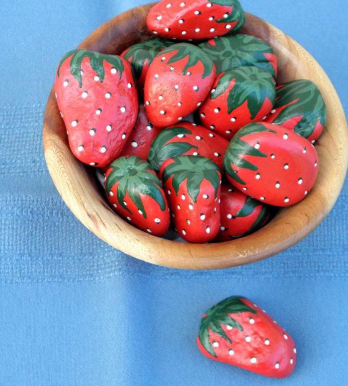 des galets peints en fraises qui semblent très réelles