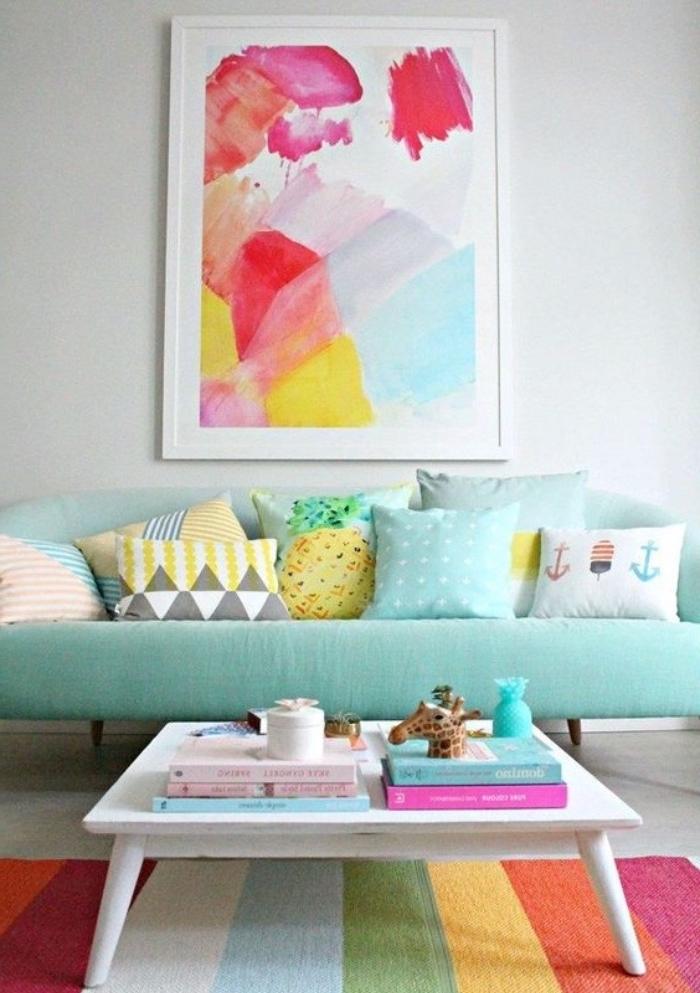 amenagement salon vert d eau, canapé bleu-vert, décoré de coussins colorés aux tons pastel, tapis à rayures multicolores, table basse en bois blanche, deco murale peinture abstraite