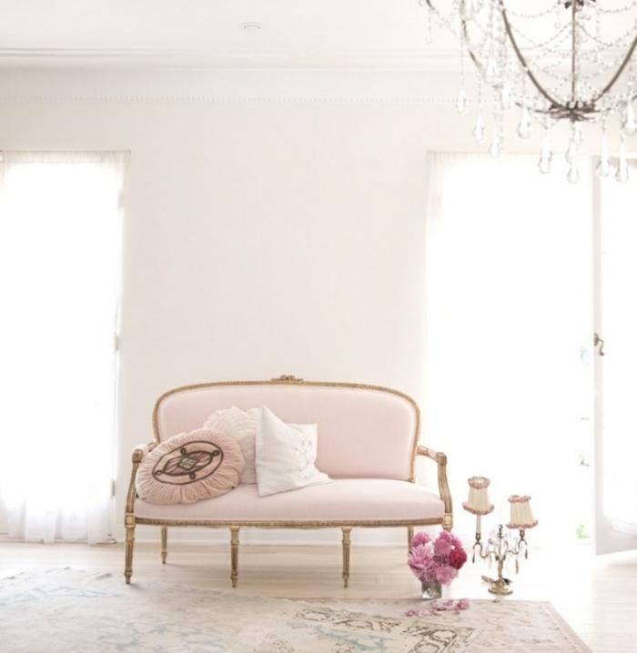 canapé shabby chic couelur rose, tapis vintage usés, bouquet de fleurs, lustre baroque et mur couleur blanche