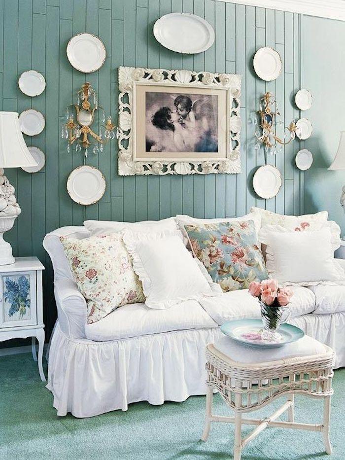 tapis et lambris bleu pastel, canapé shabby chic, habillé de housse blanche, coussins decoratifs fleuris, deco murale de vaisselle blanche, bouquet de pivoines