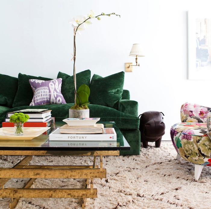 tissu velours, table basse en verre, orchidée blanche dans pot imitation marbre, canapé en velours gris, livres et magazines