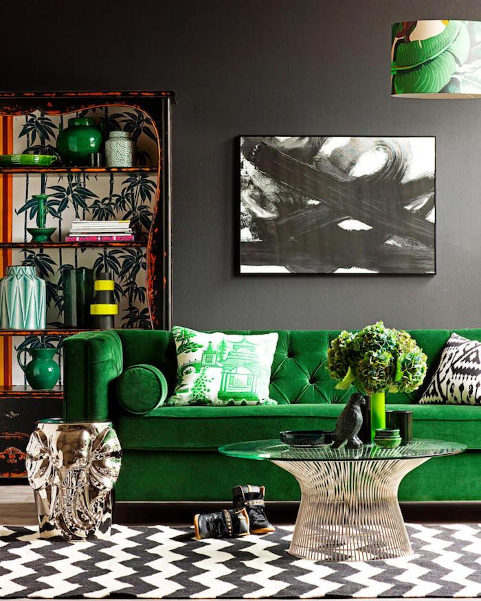 tissu velours, salon aux murs gris, bibliothèque orange à motifs tropicales, canapé en velours vert, peinture en blanc et noir