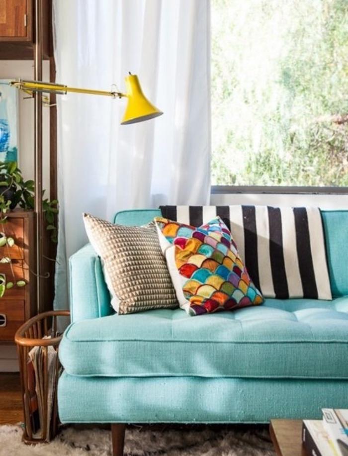 canapé couleur vert d eau,décoré de coussins colorés, meuble rangement en bois, table basse, luminaire jaune, rideaux blancs
