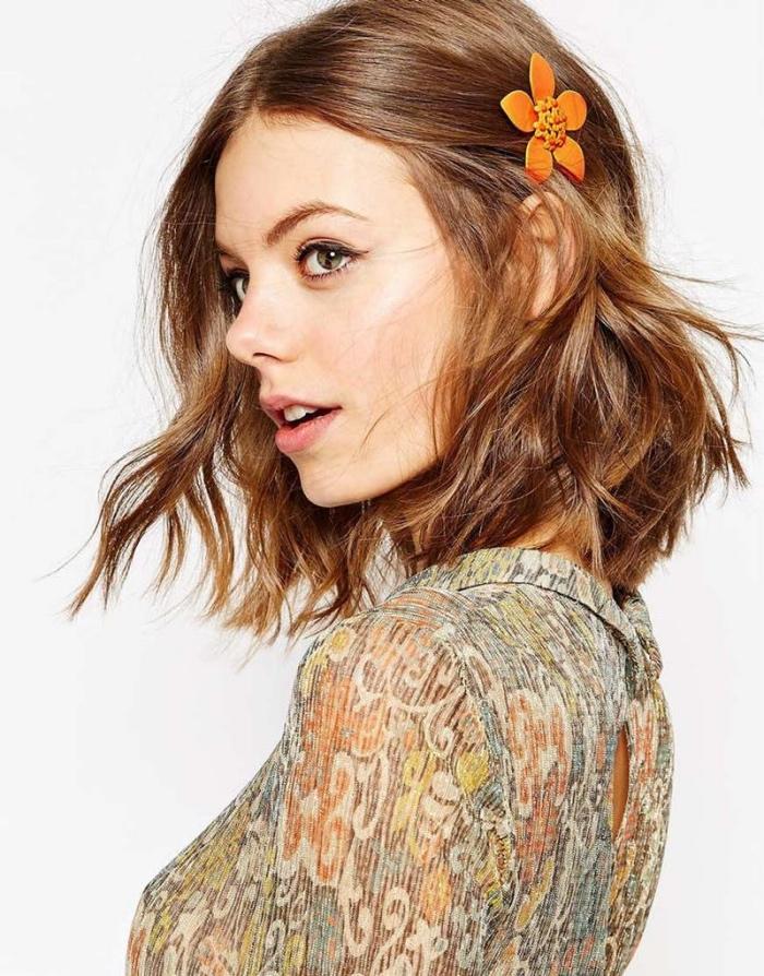 cheveux bouclés organisés en carré court ondulé, mèche de devant ramenée en arrière avec une pince a cheveux fleur orange, beach waves