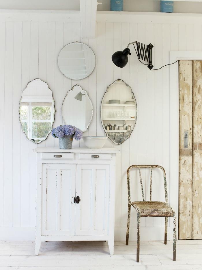 style shabby chic récup, meuble de rangement blanc, lambris blanc, deco murale de miroirs vintage, porte en planches de bois, chaise en métal rouillée