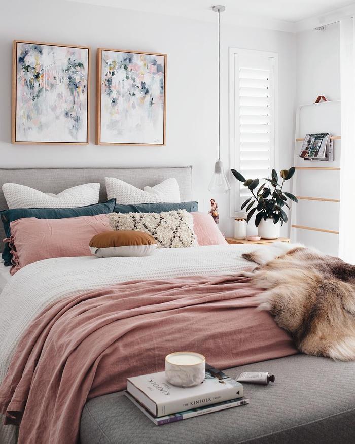 ambiance douce et féminine dans une chambre à coucher rose pastel, coussins bleu paon et rose qui reprennent les teintes des peintures