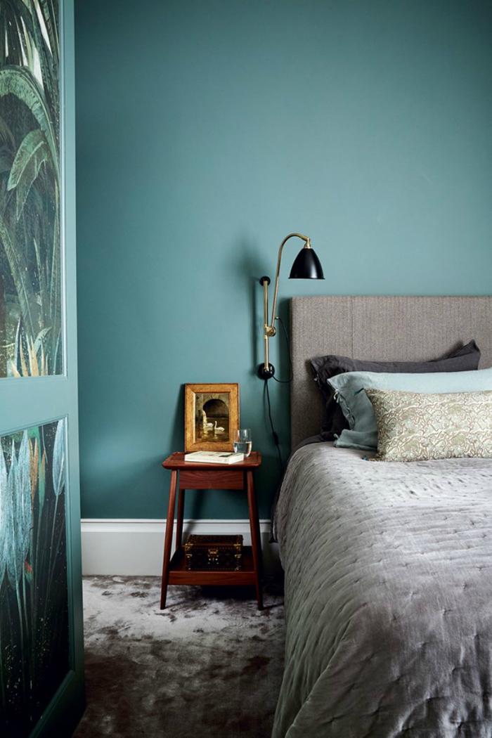 une chambre bleu paon et taupe d'une élégance sombre, ambiance apaisante grâce aux couleurs naturelles et la lumière tamisée
