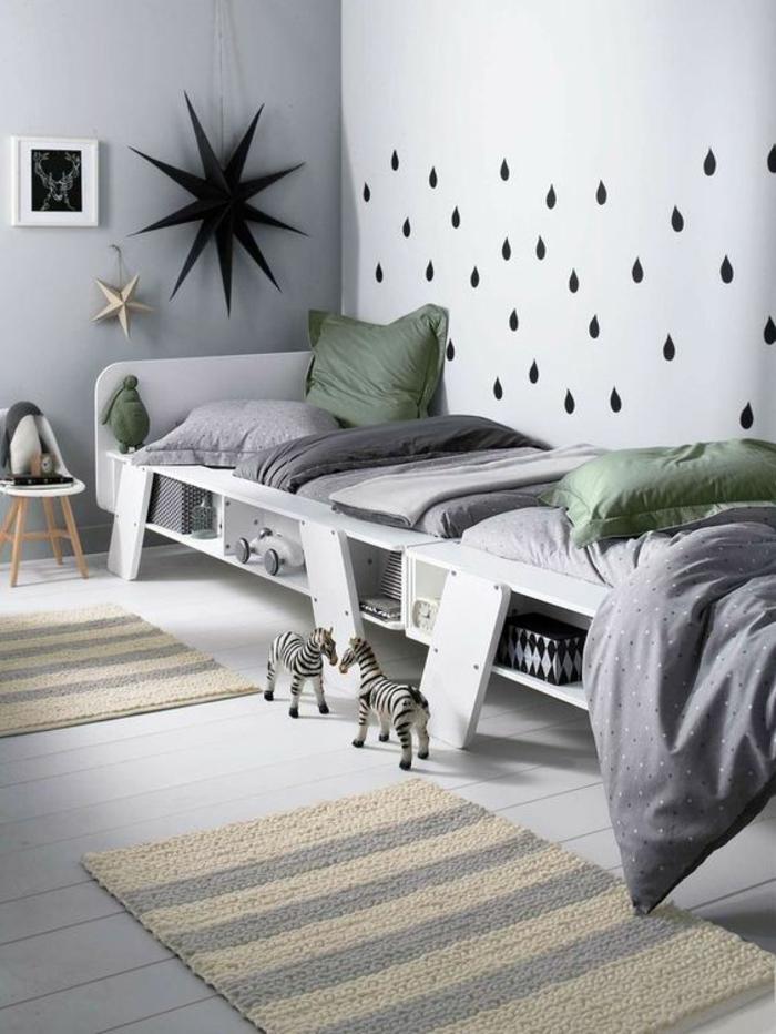 chambre design avec deux lits blancs et des coussins en vert un grande étoile noire au mur et des gouttelettes en noir