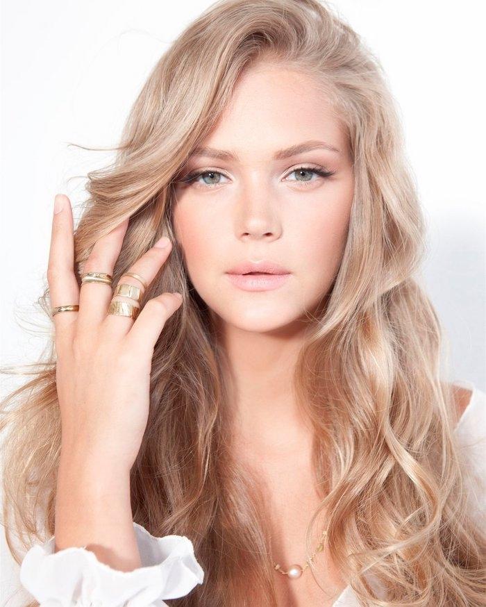 blond foncé cendré, collier en or avec petite perle, manucure nude d'ongles courts, boucles légères