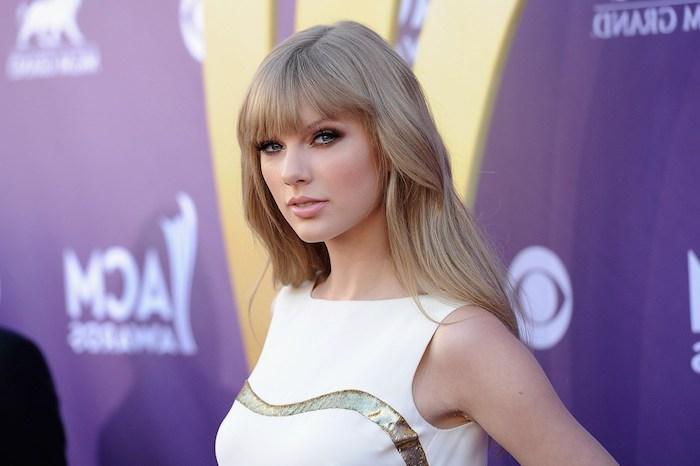 coloration cheveux, Taylor Swift, coiffure célébrité avec frange en blond cendré, maquillage yeux smoky et lèvres rose