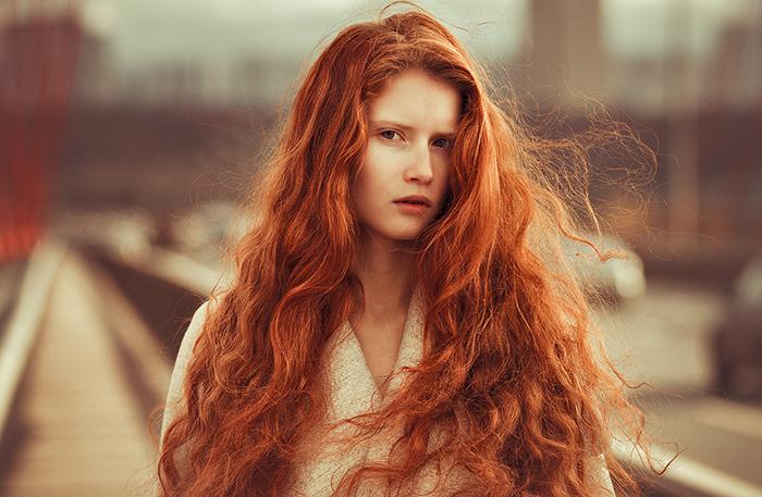 couleur cheveux cuivré, femme devant la gare, cheveux longs en orange, boucles légères, yeux marron