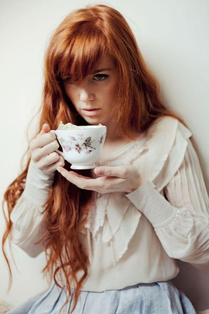 blond cuivré, tasse de café vintage en blanc, chemise en soie blanche, coiffure vintage sur cheveux orange avec frange, yeux bleus