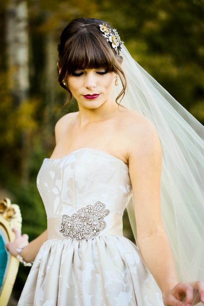 une bouche joliment dessinée teintée de couleur baie foncée, la frange élégante accentue le maquillage mariée chic