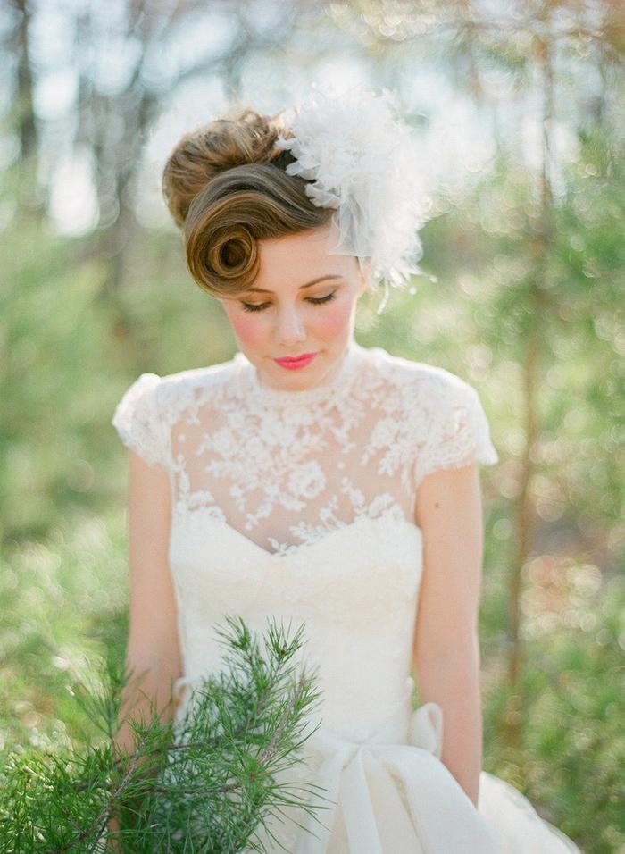 une coiffure de mariée romantique d esprit vintage, chignon rétro avec frange torsadé enjolivé par un joli accessoire en tulle