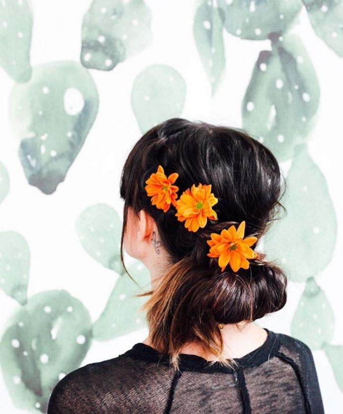 chignon bas facile a faire, décoré de trois fleurs orange, idée de coiffure féminine mariage, occasion spéciale, style boheme, champetre chic