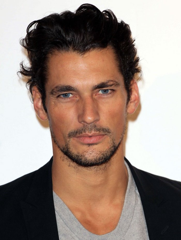 coiffure homme tendance, blazer noir et t-shirt gris pour homme, barbe noire et coupe de cheveux avec longueur sur le dessus