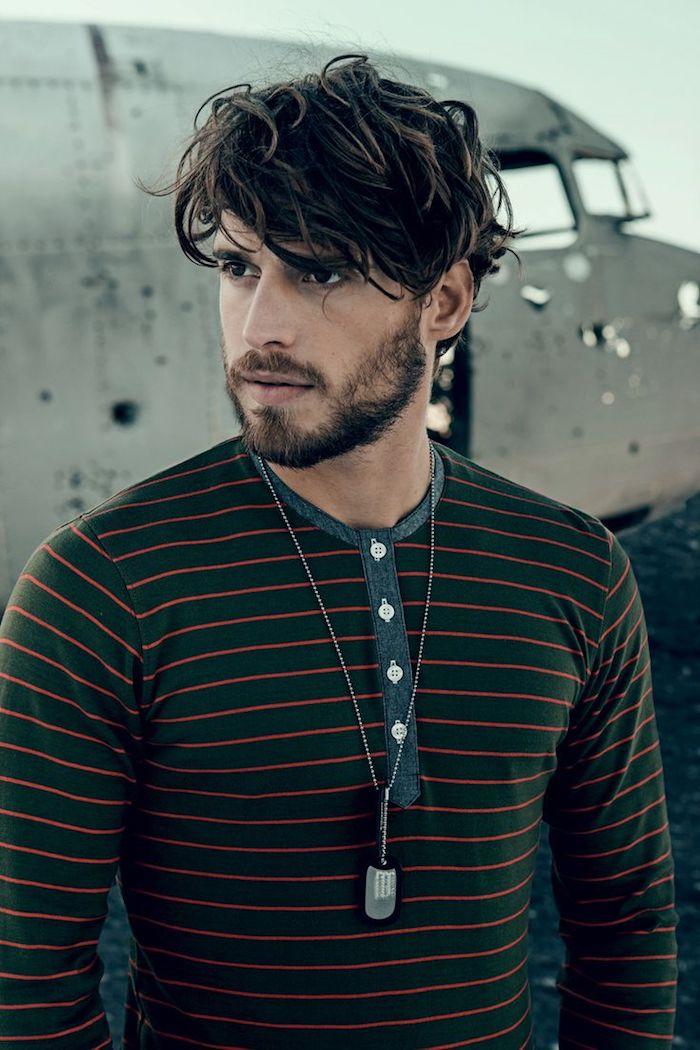 coupe de cheveux homme tendance, blouse en noir avec lignes orange, collier pour homme, coiffure cheveux ondulés