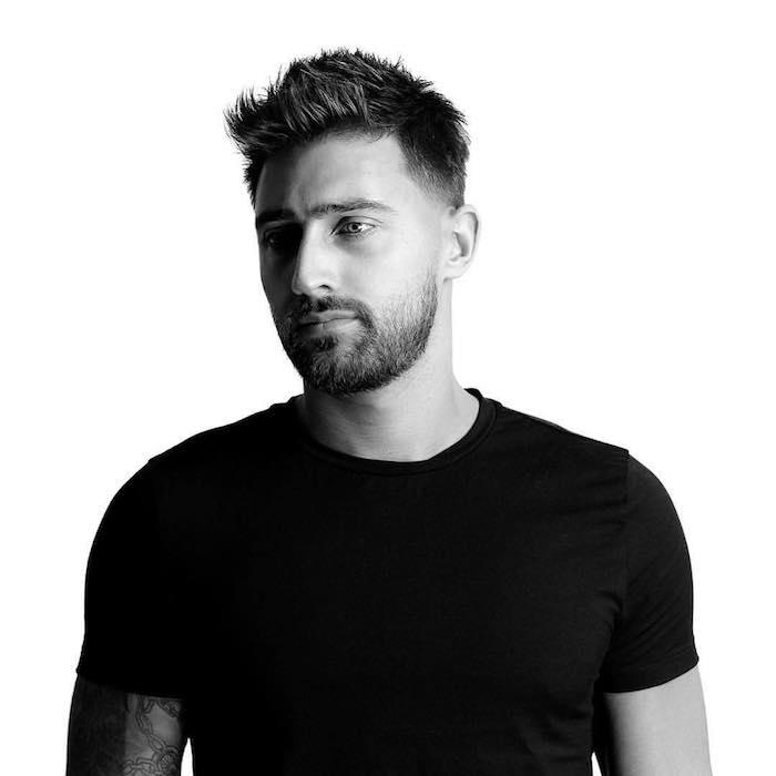 modele de coiffure, homme au t-shirt noir, tatouage chaîne sur les bras, coupe de cheveux courte pour homme