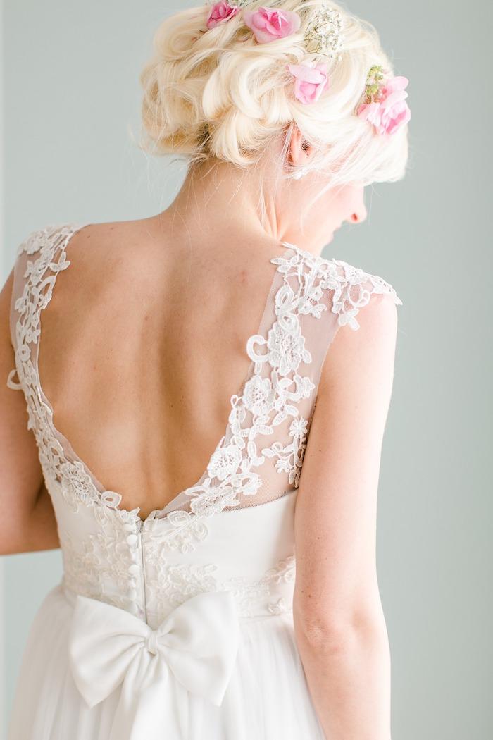 modele de coiffure, robe de mariée avec ruban sur le dos, roses dans les cheveux