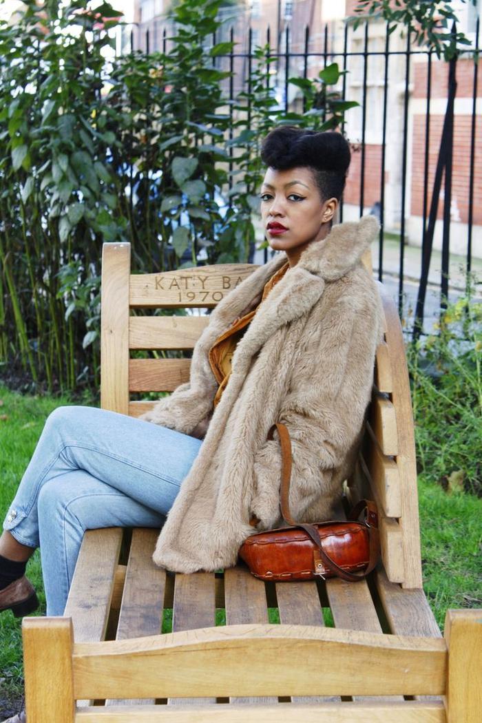 un look vintage de la tête aux pieds avec coiffure rockabilly afro, un manteau en fourrure et jeans vintage